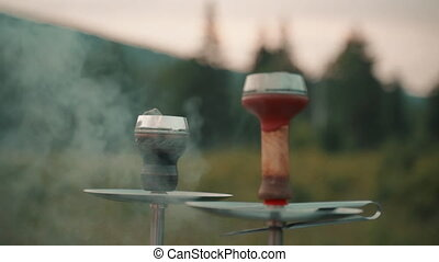 Hookah is smoked outdoors on background of nature. During picnic, there two devices for smoking pleasure. There is steam and fog when working with coal with fruit aroma. Ethnic culture for nicotine as an art. Tobacco is heated for exotic Arabic tastes.