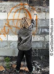 Hooligan painting graffiti on the building, vertical