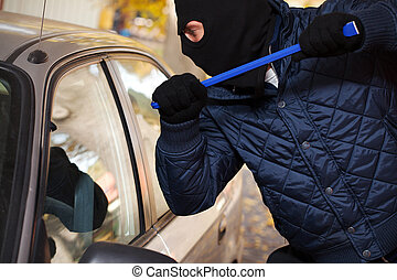 Hooligan trying to break a car's window with a crowbar
