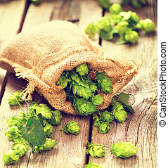 Hop in burlap bag on cracked wooden background. Brewing concept