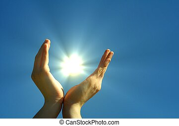 hope and freedom - hand sun and blue sky showing hope peace...