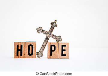 Hope in wooden block letters with silver cross on white...