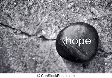Hope  - The word hope on a zen stone against concrete
