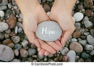 Woman holding stone with the word Hope in her palms