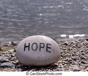 the word hope written on a small rock with the peaceful ocean waves in the background.