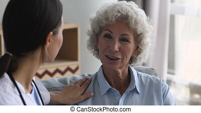 Hopeful older hoary woman talking to attentive young doctor...