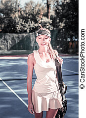 Hopeful pleasant woman getting ready for tennis