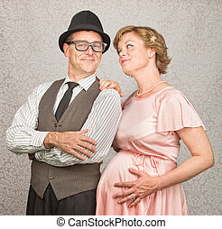 Hopeful Pregnant Couple - Man with folded arms and happy...