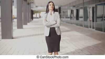 Hopeful woman with folded arms near building