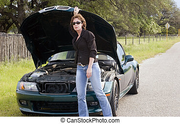 A mature distress woman standing in front of a vehicle that appears to be having some sort of mechanical failure.