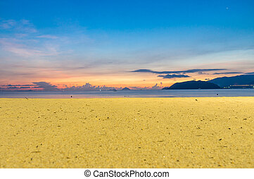 Horizon at colorful sunrise on the beach with yellow sand and blue sky