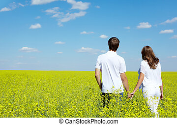 Horizons of hope - Back view of amorous couple walking in...