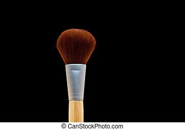 Horizontal close up of a make-up brush on black