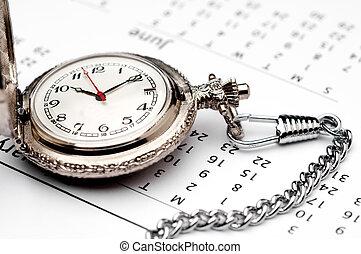 horizontal close up of a pocket watch on a calendar