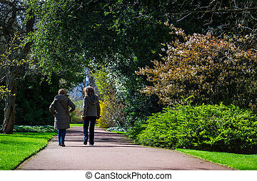 Horizontal colour image of 2 female friends taking a walk in...