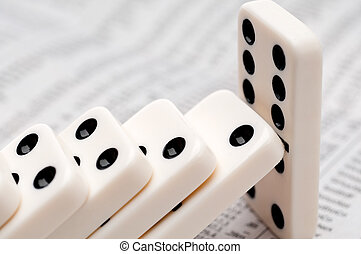 Horizontal image of falling dominoes on a newpaper stock report