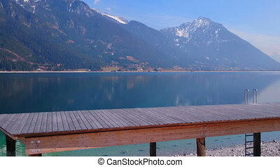 """Horizontal pan of wooden pier near beautiful lake, mountains covered with snow"""