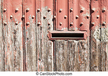 horizontal part of wooden door with old bladdered gray paint and metal handle