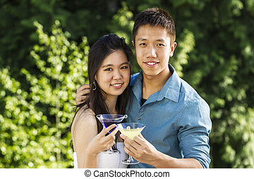Horizontal photo of a young adult couple, front view,  holding drinks while outdoors with green trees in background