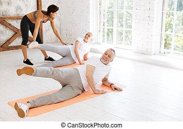 Horizontal photo of attentive man that lifting his leg