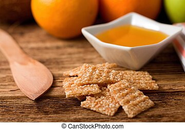 Broken sesame wafers in front of bowl with honey