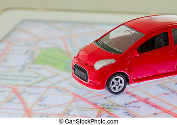 horizontal photo of closeup red car toy on the map in tablet screen