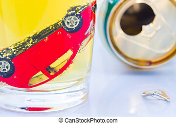 horizontal photo of red toy car in a glass of beer isolated on white background. Drunk-driving Prevention Concept