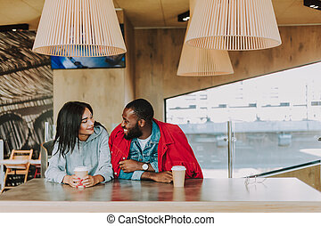 Horizontal photo of two people drinking coffee and talking