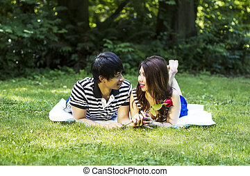 Horizontal photo of young adult couple, lying on blanket, while looking at each other with green grass and trees in background