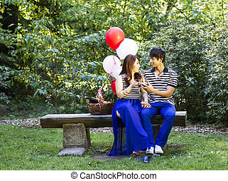 Horizontal photo of young adult couple sitting on log bench with glasses filled with red wine being held in their hands with balloons, green grass and trees in background
