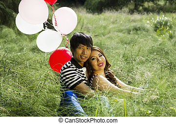 Horizontal photo of young adult couple, looking forward, sitting in the middle of a green tall grass field with several red and white balloons behind them