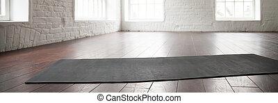 Horizontal photo yoga mat on wooden floor at sport club