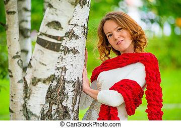 Horizontal portrait of a beautiful girl on nature near the tree