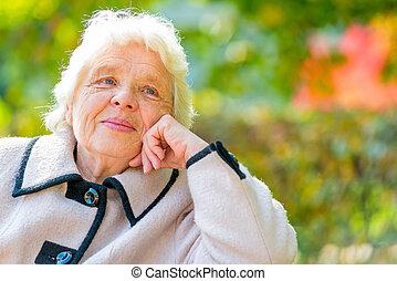 Horizontal portrait of a beautiful pensioner on nature backgroun