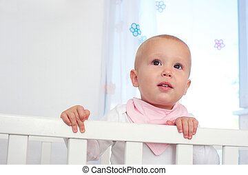 Horizontal portrait of a cute baby in crib