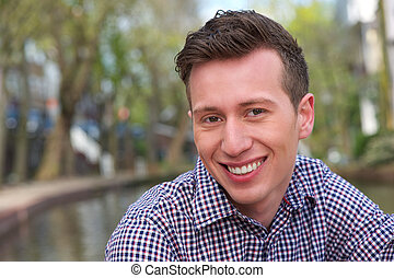 Horizontal portrait of a handsome young man smiling outdoors