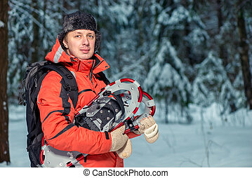 horizontal portrait of a male tourist with snowshoes in the winter forest