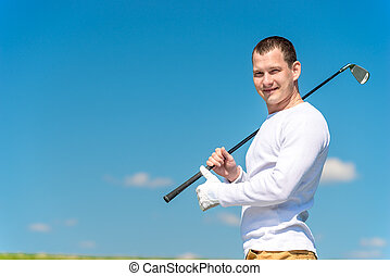 horizontal portrait of a successful golfer with a golf club on the field