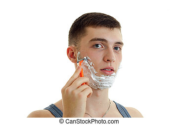 horizontal portrait of a young guy with foam on his face which seriously shaves his beard machine