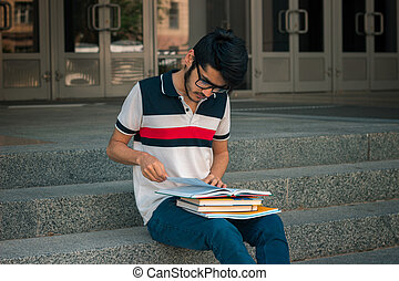 horizontal portrait of a young handsome guy with books