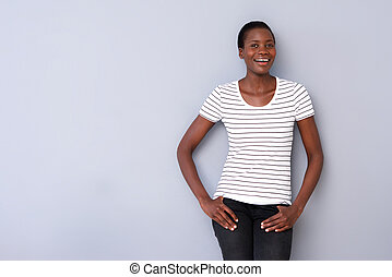portrait of beautiful african woman posing on gray background and smiling