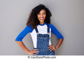 portrait of smiling young african american woman against gray wall
