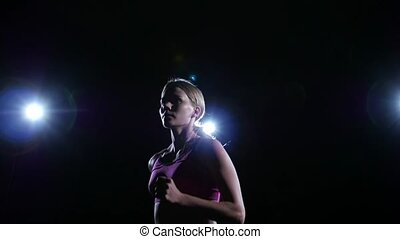 Horizontal shot from right to left running girl backlit on...