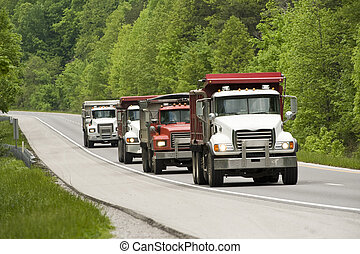Horizontal shot of Dump Trucks On Highway. Greenery on the sides of the road.