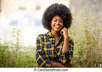 Horizontal smiling young black woman with afro hair outdoors