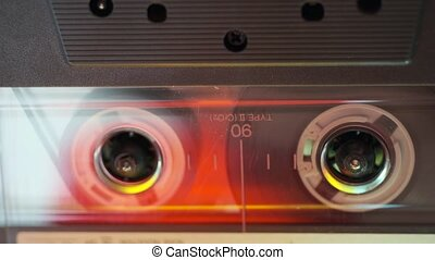 horizontal tracking footage of transparent audio cassette playing