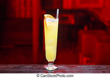 Closeup of a long glass of orange juice with gin, which sits on the bar counter, isolated on a red light background.
