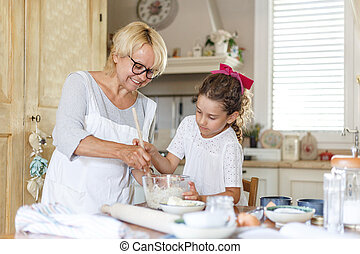 Horizontal view. Grandmother and adorable little curly granddaughter in the kitchen, they are preparing together.