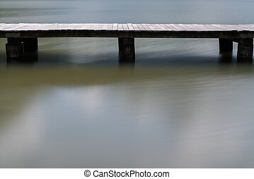 long wooden boardwalk on a calm and placid mountain lake abstract view with copy space
