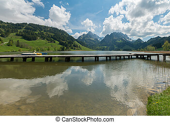 long wooden boardwalk on a calm and placid mountain lake with a great view